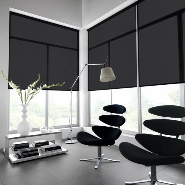 Black roller blinds in an office