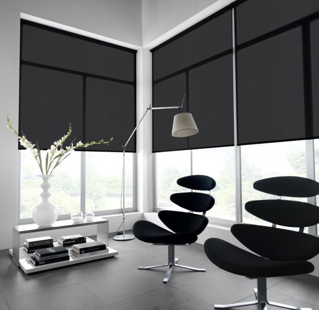 Black roller blinds in an office
