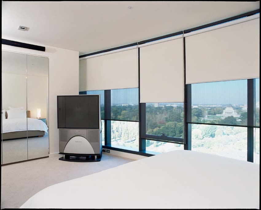 White motorised roller blinds in a bedroom