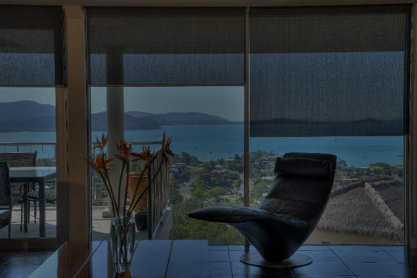 Blinds covering a huge glass window overlooking an amazing seascape